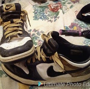 A Pair of Gold & Black Nike Shoes